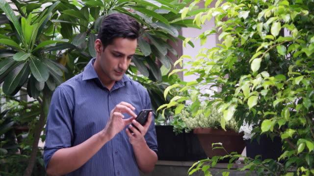 vídeos y material grabado en eventos de stock de man busy with his cellphone, pan right - formal garden