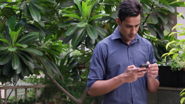 vídeos y material grabado en eventos de stock de man busy with his cellphone, tilt up - formal garden