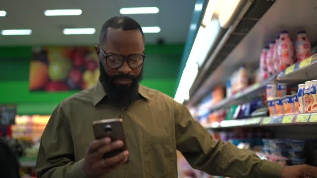 man buying at supermarket using mobile phone - price tag stock videos & royalty-free footage
