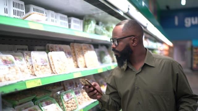 vídeos de stock, filmes e b-roll de homem compra em supermercado usando celular - consumismo