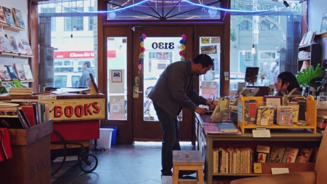 man buying book in bookstore - credit card purchase stock videos & royalty-free footage