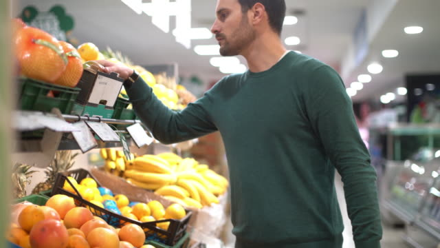 vídeos de stock e filmes b-roll de man buying fruit in supermarket. - fazer compras
