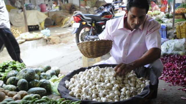 MS Man buying garlic at vegetable store in market / Gurgaon, Haryana, India