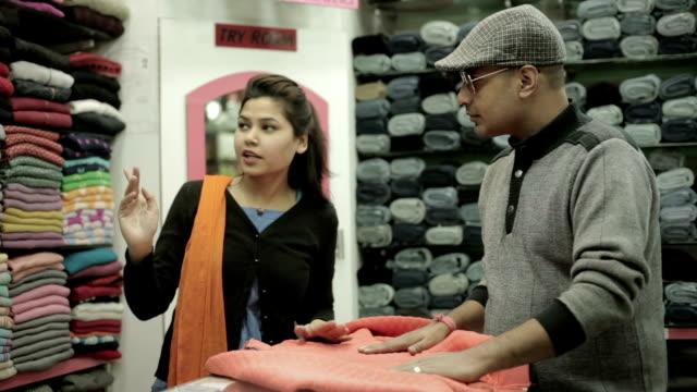 vídeos de stock, filmes e b-roll de homem comprando roupas para a família e a vendedora confiante a ajudá-lo. - índia
