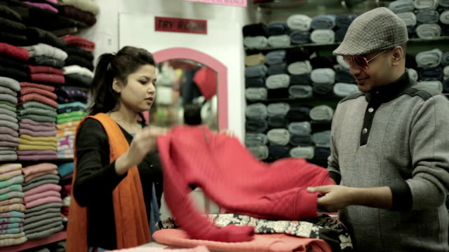 man buying garments for family and confident saleswoman helping him. - warm clothing stock videos & royalty-free footage