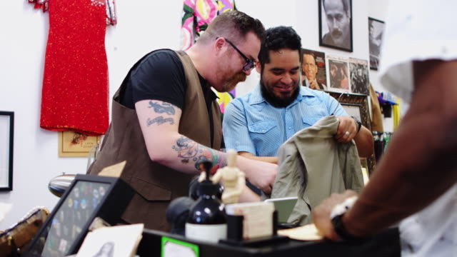man buying jacket in locally owned clothing store - clothes shop stock videos & royalty-free footage