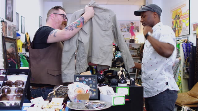 man buying jacket in vintage clothing store - real people stock videos & royalty-free footage