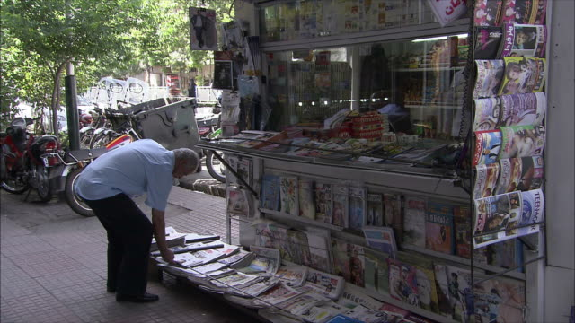 vidéos et rushes de ms zi man buying newspaper in kiosk, tehran, iran - kiosque à journaux
