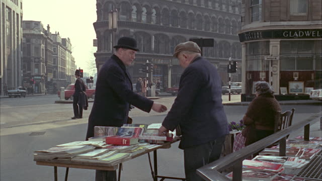 vidéos et rushes de 1966 ms man buying newspaper on street book stall / london, united kingdom - acheter