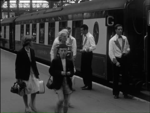 vidéos et rushes de  ms man buying tickets and views of busy platform and station / bighton, sussex, england  - 1950 1959