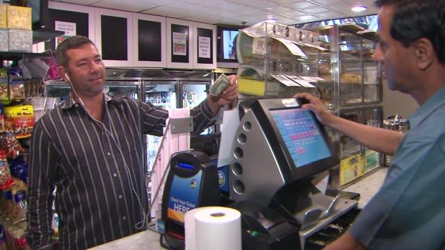 stockvideo's en b-roll-footage met man buys a lottery ticket on august 01, 2013 in new york, new york - loterijlootje
