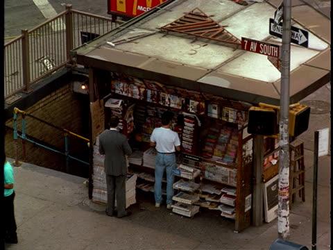 vídeos de stock, filmes e b-roll de a man buys a newspaper at a street vendor stand. - escrita ocidental
