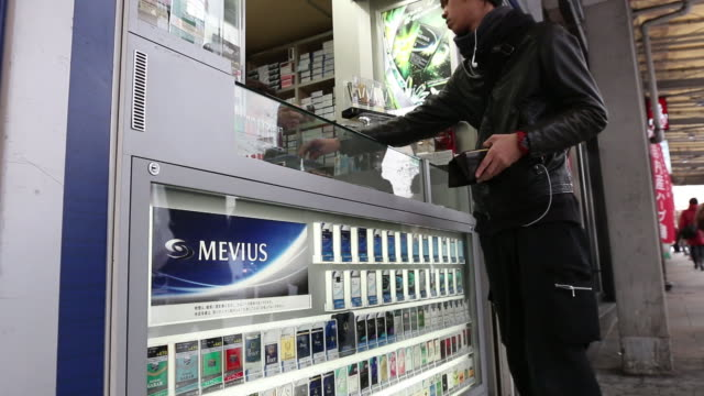 vídeos y material grabado en eventos de stock de a man buys a pack of cigarettes at a store next to vending machines selling packets of mevius brand cigarettes pull focus into mevius brand... - vender