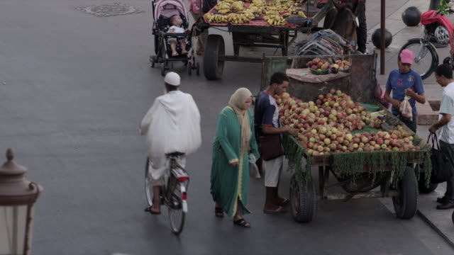 Man buys apples from street vendor, then looks at bananas