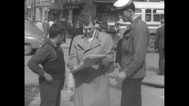 man buys newspaper from boy on city street as extremely tall sailor looks on / overtheshoulder shot of winnipeg tribune headline about the red river... - fluss red river stock-videos und b-roll-filmmaterial