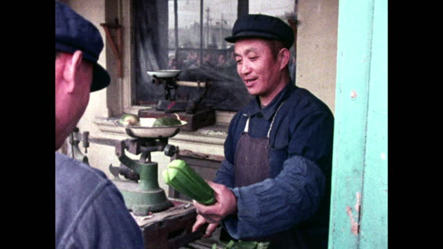 man buys sliced cucumber from food concession stand in beijing; 1973 - news not politics stock videos & royalty-free footage