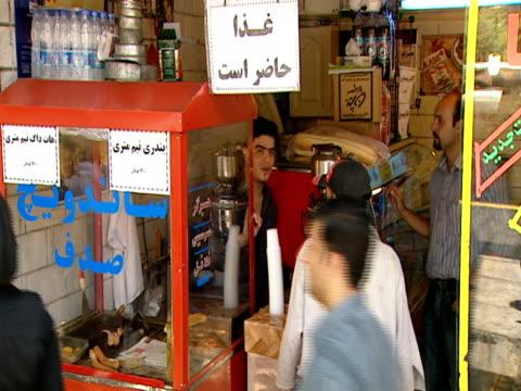 vidéos et rushes de man buys something to drink at a market stand / tehran, iran - format vignette