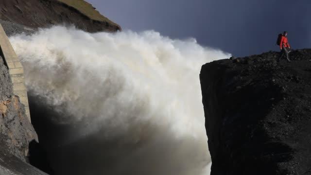 vídeos de stock, filmes e b-roll de a man by the overflow from the karahnjukar hydro project, iceland. - forma da água