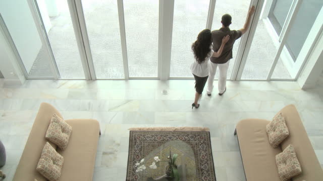 man by window waiting for woman, she enters and they embrace then leave together - ricchezza video stock e b–roll