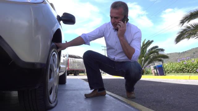 vídeos de stock, filmes e b-roll de homem chamando o seguro por causa de um pneu - baixo posição