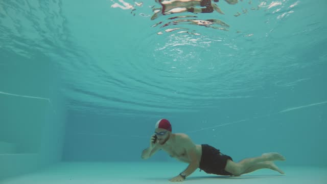 Man calling underwater with mobile phone