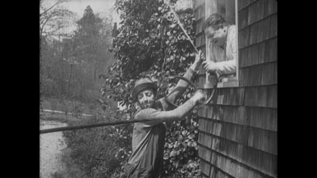 1917 man (fatty arbuckle) calls on the gardener for help to put out the fire with his hose - squirting stock videos and b-roll footage