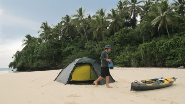 MS A man camped on a Pacific island with a kayak