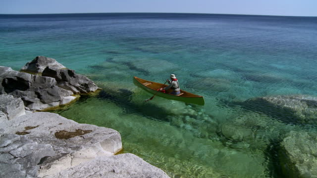 WS PAN Man canoeing at Georgian bay shoreline / Tobermory, Ontario, Canada