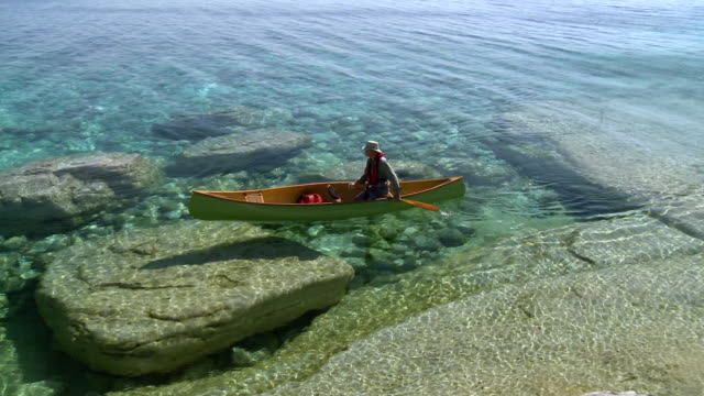 ws pan man canoeing at georgian bay shoreline / tobermory, ontario, canada - ontario canada stock videos and b-roll footage