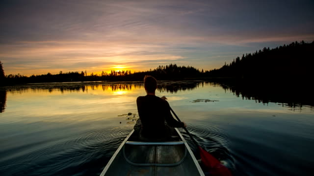 Man canoeing at sunset