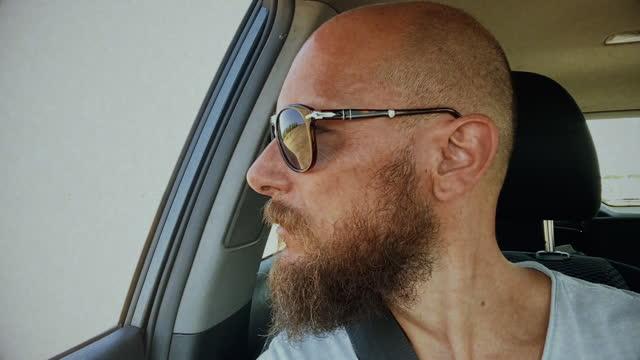 vidéos et rushes de passager de voiture d'homme avec la vidéo de selfie de lunettes de soleil - photophone