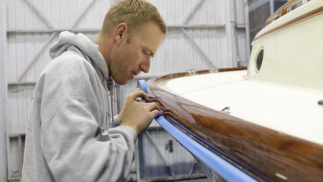 CU Man carefully applying tape to mask an area for varnish on boat.