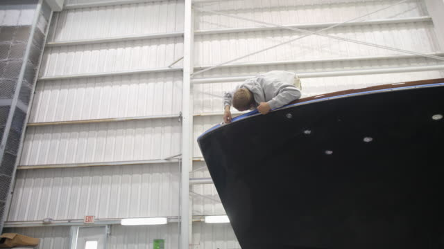 WS Man carefully applying tape to mask an area for varnish on boat.
