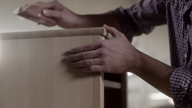 man carpenter using sandpaper for finishing work on piece of furniture - carpenter stock videos & royalty-free footage