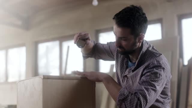 mann zimmermann mit sandpapier für die endbearbeitung auf möbel - schreiner stock-videos und b-roll-filmmaterial