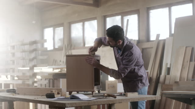 Man carpenter using sandpaper for finishing work on piece of furniture