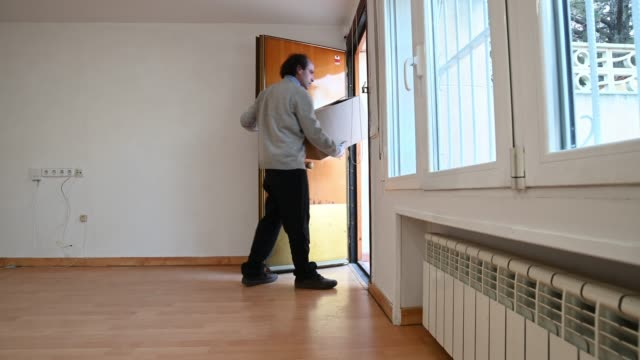 man carries a box, leaves and then enters the house through the door - tenant stock videos & royalty-free footage