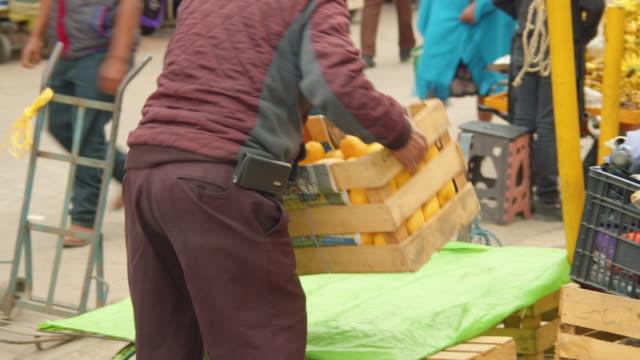 vídeos de stock e filmes b-roll de man carries a crate of ripe mangoes for sale at a local market in san cristobal de las casas, chiapas, mexico - chiapas