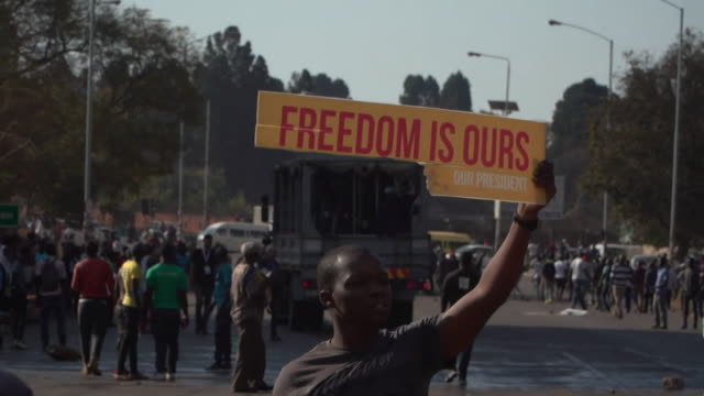 a man carries a 'freedom is ours' sign in harare during riots in the city - zimbabwe stock videos & royalty-free footage