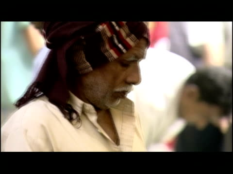 vidéos et rushes de a man carries a large bundle of flowers through a busy marketplace in kolkata. - coiffe traditionnelle