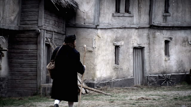 a man carries a satchel and walking stick as he travels through an abandoned village. - satchel stock videos & royalty-free footage