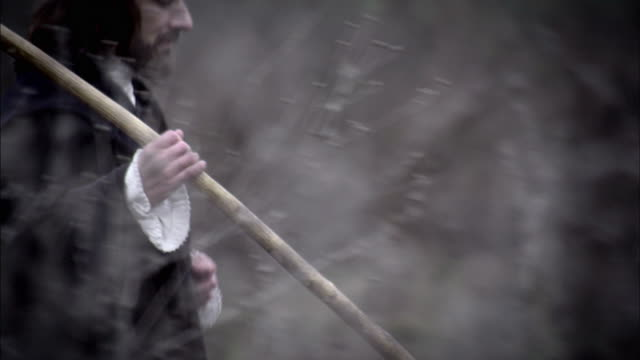 a man carries a walking staff as he treks across a field. - reenactment stock videos & royalty-free footage