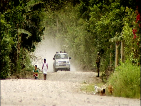 vidéos et rushes de man carries banana leaves across road as 4x4 travels along in distance colombia - colombie