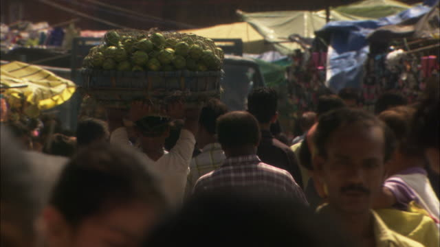 man carries basket of produce on head along busy street available in hd. - basket stock videos & royalty-free footage