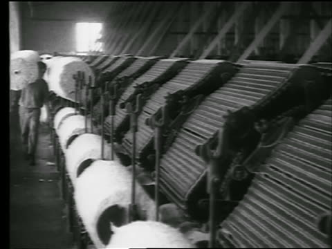 B/W 1922 man carries bolts of cotton + puts it on spool of machinery in cotton mill