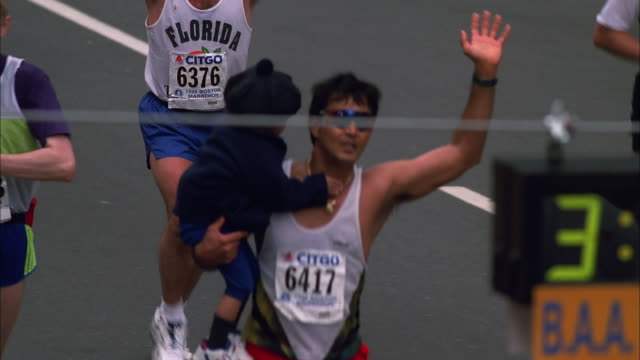 vídeos de stock e filmes b-roll de man carries child and waves to crowd while running to finish line at boston marathon, massachusetts available in hd. - acabar