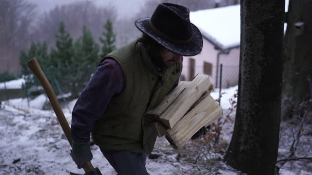 stockvideo's en b-roll-footage met man carries firewood up trail from mountain cabin with an axe in hand - alleen één mid volwassen man