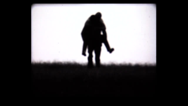 1968 man carries girl on back, approaches camera - teenage couple stock videos & royalty-free footage
