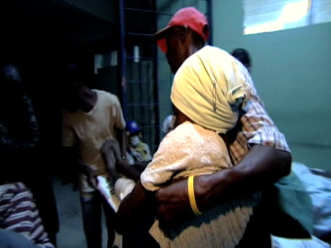 vídeos de stock e filmes b-roll de man carries injured woman through hospital corridor at night following devastating earthquake in haiti 14 january 2010 - hispaniola