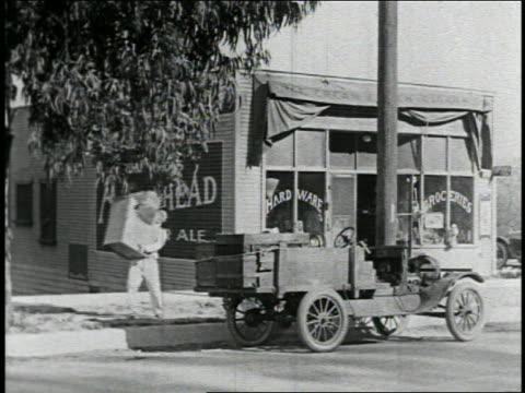 B/W 1925 man carries large box to truck / it drives off + he falls as he tries to load box / feature